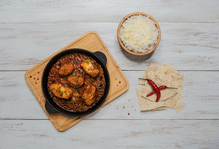 Bengali fish curry and set Indian spices with basmati rice on wooden table
