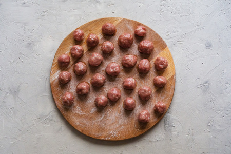 Balls of minced meat on a wooden Board before cooking. Meat meatballs Imagens