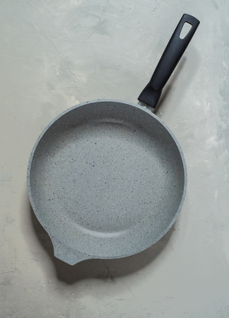Grey stone pan on grey table. Top view Imagens