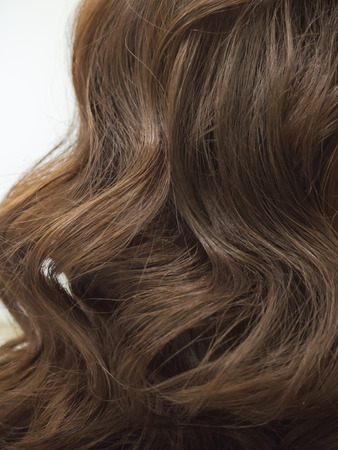 Brown curls of hair, female hairstyles. Close up