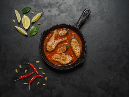 Vista superior de curry de pescado bengalí picante y caliente. Comida india. Pescado al curry con ají rojo, hoja de curry, leche de coco. Cocina asiática.