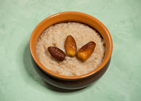 Healthy food. Oatmeal with dates on the green table.