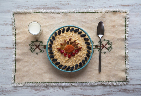 Oatmeal porridge with dried fruits on a wood table. Top view. Reklamní fotografie