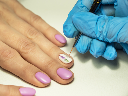 Installing rhinestones on nails in beauty salons. Close up. Reklamní fotografie