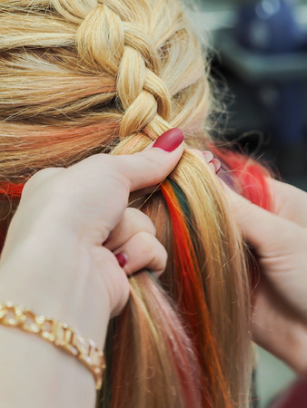 Rainbow hair in a braid. Braiding close up 스톡 콘텐츠
