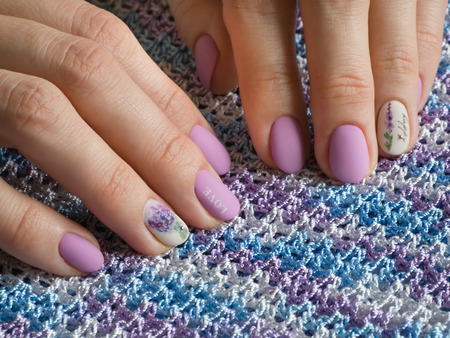 Fashionable lilac manicure design in the hand on a color background.