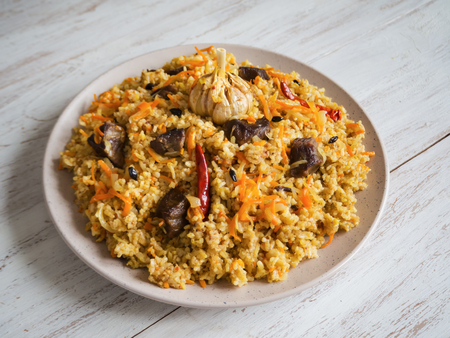 Uzbek pilaf in a plate on a white wooden table. Top view. Stock Photo