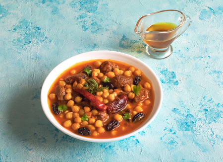 Stewed meat with bulgur and chickpeas in red sauce with dates and raisins. Stockfoto