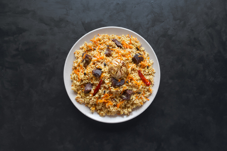 Meat Biryani in a plate on a black table. Top view.