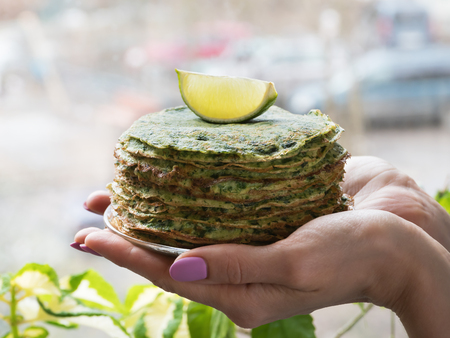 Spinach pancakes in the hands of the window Stok Fotoğraf