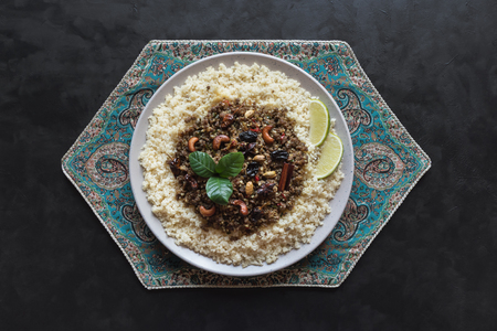 Moroccan spiced mince with couscous in a plate on black background.