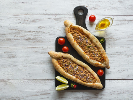 Arabic pizza Lahmacun on white wooden background