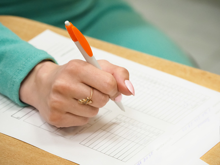 Woman signing document, close up on female hand holding pen and paper on table. Selective focus. Stock Photo