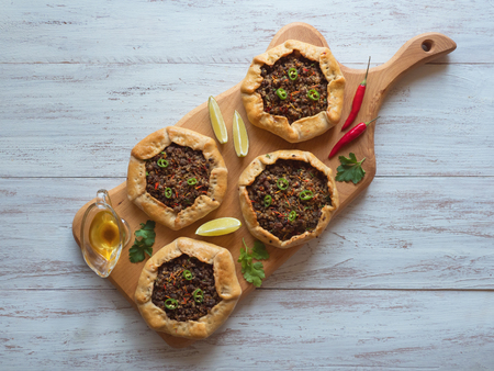 Open meat pies on a wood background. Top view