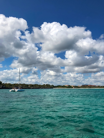 Turquoise sea background with clouds, sky and with catamaran on ripples the water. Standard-Bild