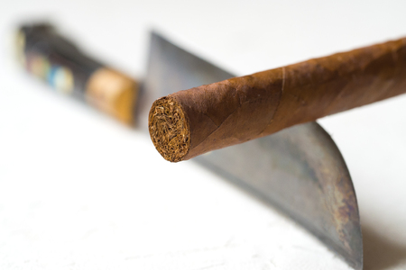 Cigar balancing on a knife edge. The concept of dangers of smoking. Stock Photo
