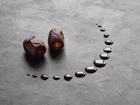 Black Ramadan background with dates and dates syrup poured in the shape of crescent moon. 版權商用圖片