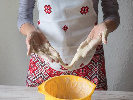 Schlechter Teig. Küchenkatastrophe und schlechtes Kochkonzept. Verärgerte Frau behält klebrigen Teig Standard-Bild