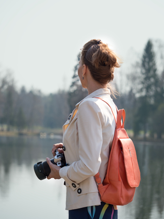 Girl photographer with a backpack walking in nature.