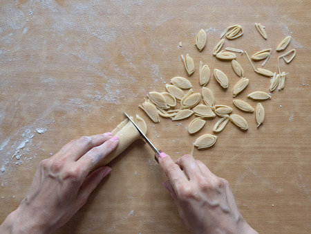 Hand slicing homemade noodles. Top view