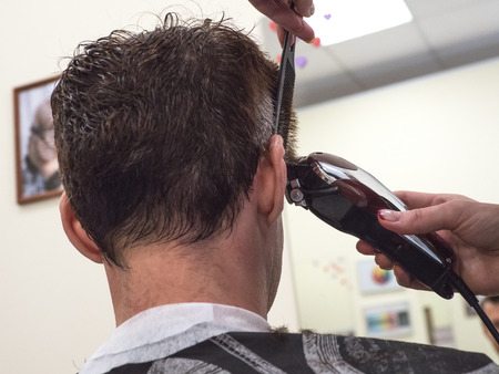 Barber trim Caucasian man client with clipper machine in barbershop. Male beauty treatment process in close up. Stockfoto