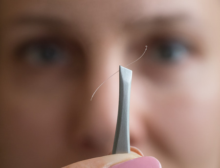 Tweezers with gray hair in front of the woman face.