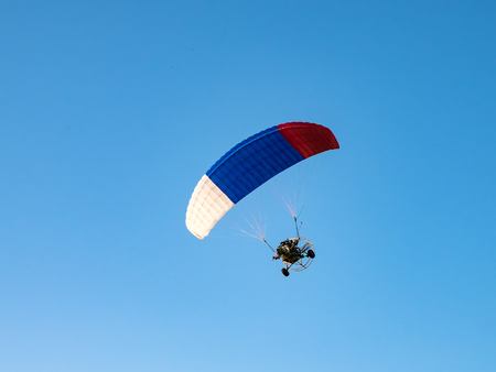 Extreme sports. Powered parachute against the blue sky.
