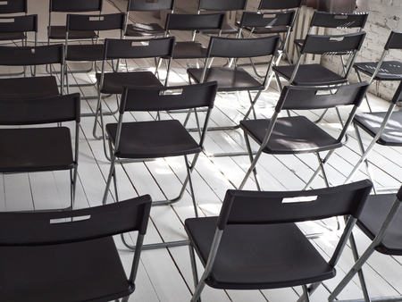 Black folding chairs stand in rows in the white conference room