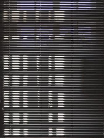 Dark blinds close the sunny window. Dark window background