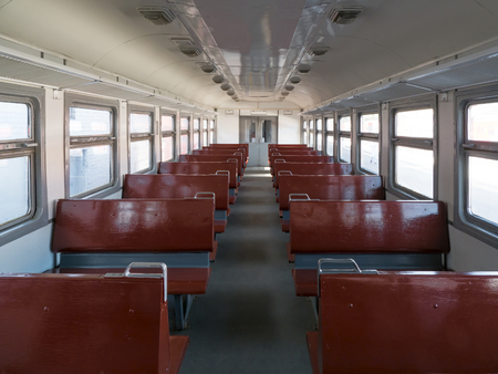 Empty train car with seats perspective.