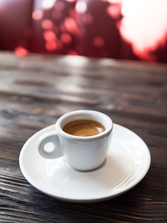 Coffee in a white cup stands on a wooden table Stock Photo