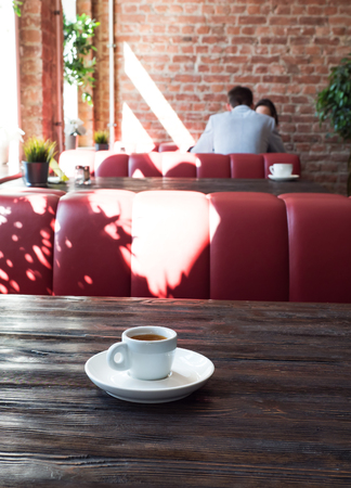 A date in a cafe. A cup of coffee on the table with two people talking.