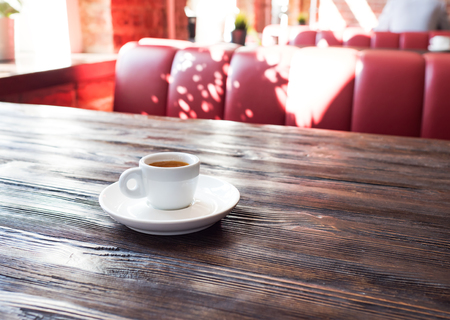 Coffee in a white cup stands on a wooden table.