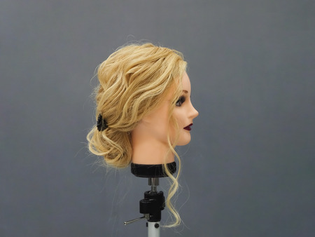 Mannequin head with European textured hair on a gray background.