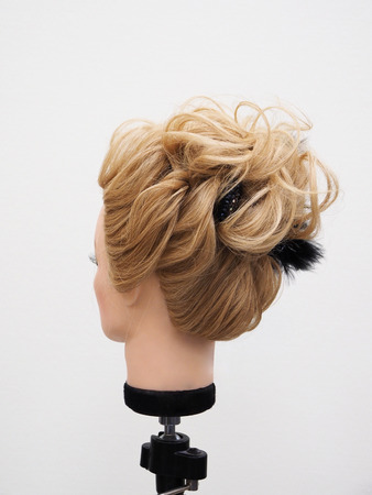 European hairstyle on the head of a mannequin on a light background.