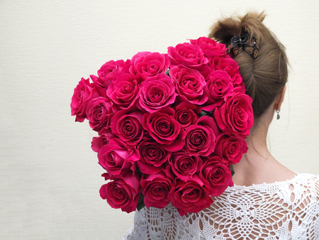 The bride standing back holding a large bouquet of roses on his shoulder. Stock Photo