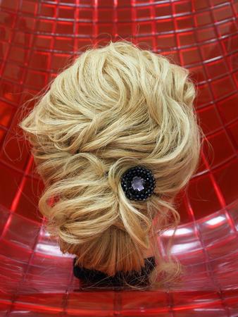 Peinado europeo en la cabeza de un maniquí sobre un fondo rojo. De cerca. Foto de archivo