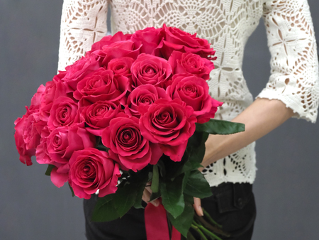 Bouquet of red roses behind her back, close up Stock Photo
