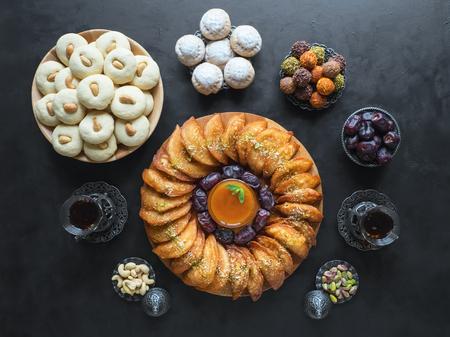 Ramadan food background. Arabic sweets. Arabian Qatayef, Ghorayeba sweets and Egyptian cookies Kahk El Eid. Cookies of El Fitr Islamic Feast.