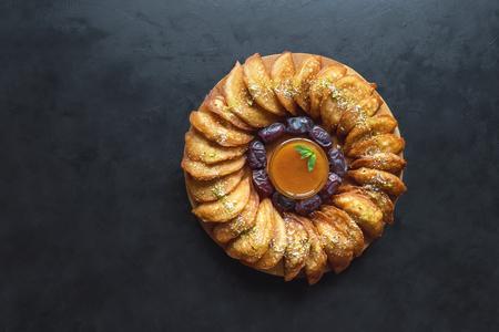 Arabian Qatayef pancake stuffed with sweet cheese and nuts on the black table.
