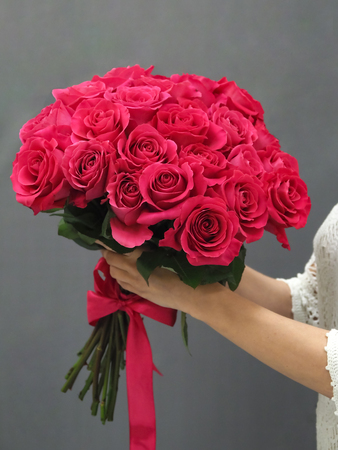 Bouquet of red roses in her hands, close up