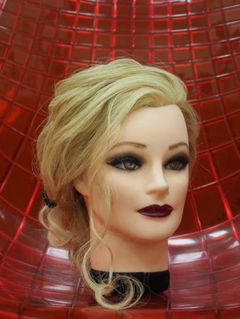 European hairstyle on the head of a mannequin on a red background. Close up.