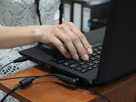 Businesswoman working on a laptop in the office. Close-up of the hand at the keyboard. Stock Photo