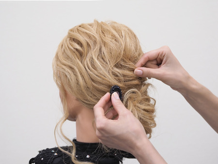Haarstyling an einer Schaufensterpuppe trainieren. Erstellen von Frisuren auf einer Schaufensterpuppe. Standard-Bild