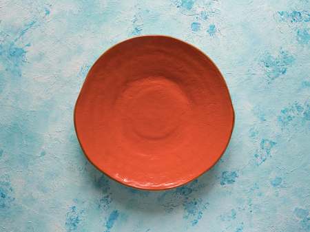 Orange ceramic plate handmade on blue background.