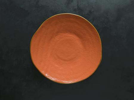 Orange ceramic plate handmade on black background