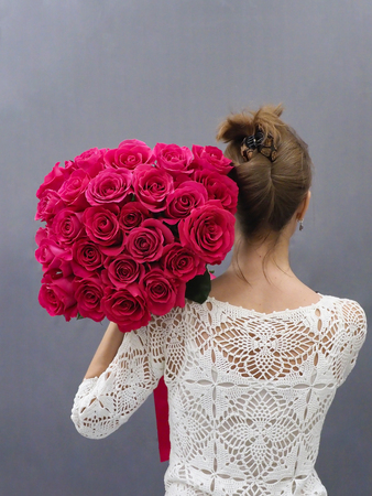 A bouquet of red roses on the bride shoulder.