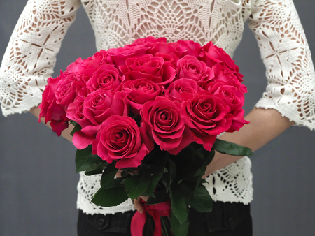 Bouquet of red roses behind her back Stock Photo