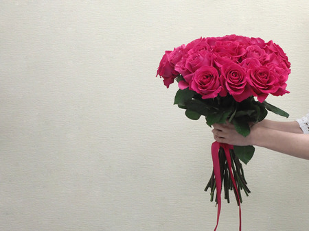 Bouquet of red roses in womens hands.