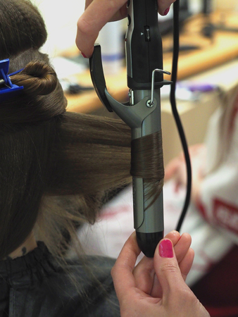 Twisting strands on the curling in the beauty salon.